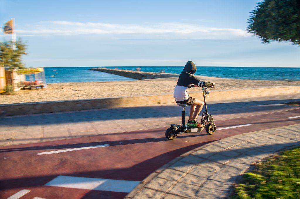 Guy riding electric scooter along autumn beach.