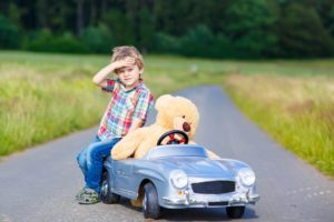 Little kid boy driving big toy car with a bear, outdoors.